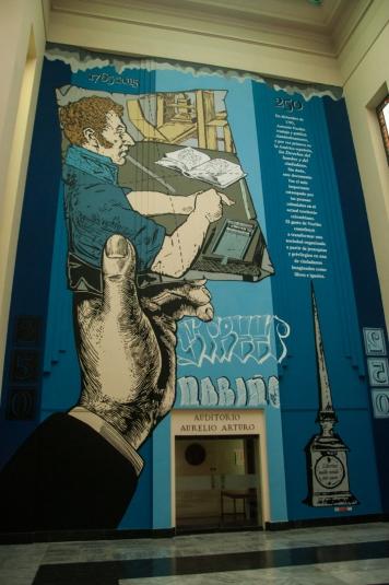 Y luego Toño el impresor hecho por Lesivo es el tercer mural que se disfruta. El artista, quien inspiró su obra en las investigaciones adelantadas por Alexander Chaparro y un equipo de la biblioteca, nos recuerda por medio de ella que la información adquirida debe ser para imprimir y publicar. Y por supuesto, divulgar, como lo evoca el título de esta revolucionaria exposición.
